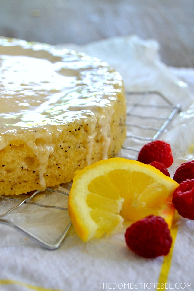 lemon poppyseed cake on wire rack with lemon slice and fresh raspberries