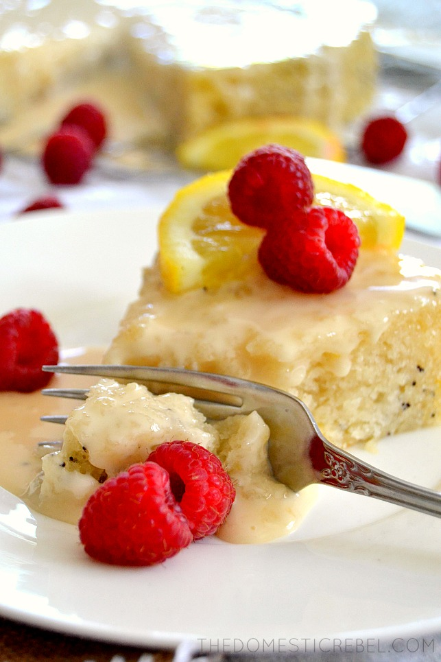 lemon poppyseed cake on white plate with fork and raspberries