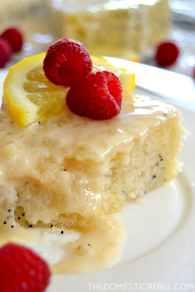 closeup photo of lemon poppyseed cake with fresh lemon and raspberries on white plate
