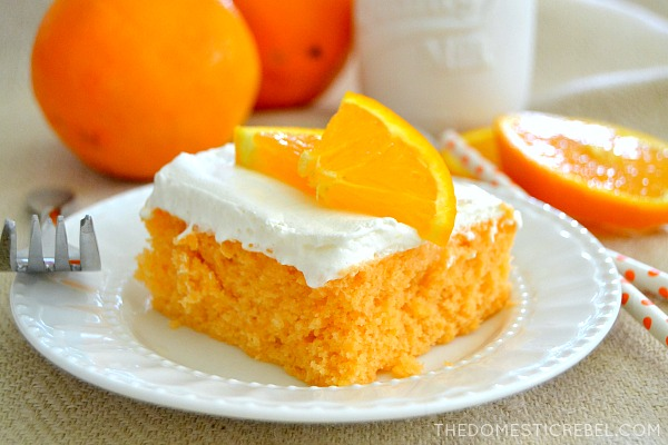 orange creamsicle cake on white plate with fork and oranges in background