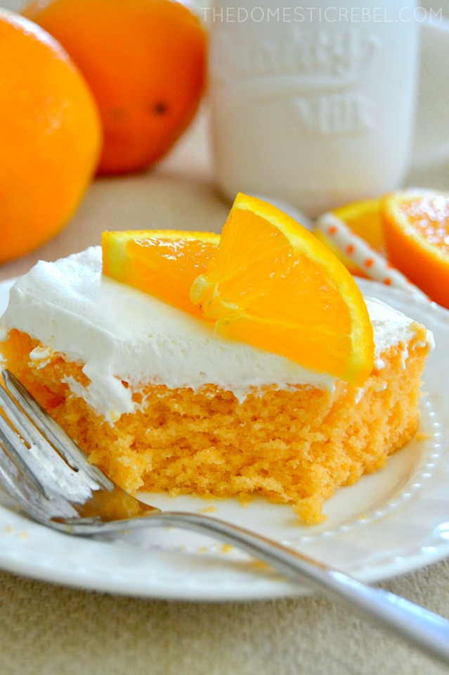 orange creamsicle cake on white plate with fork and bite missing