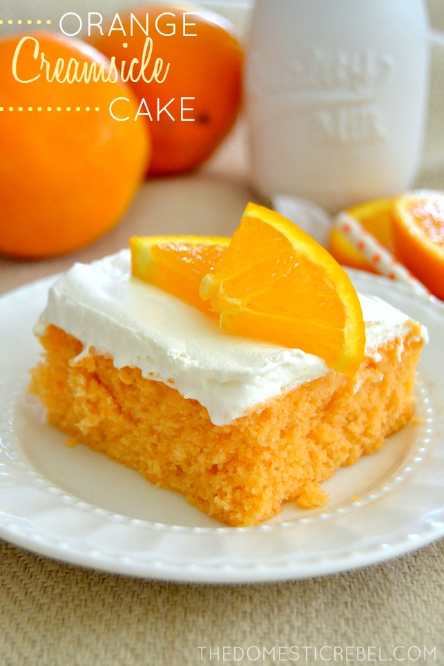orange creamsicle cake on a white plate with oranges in background