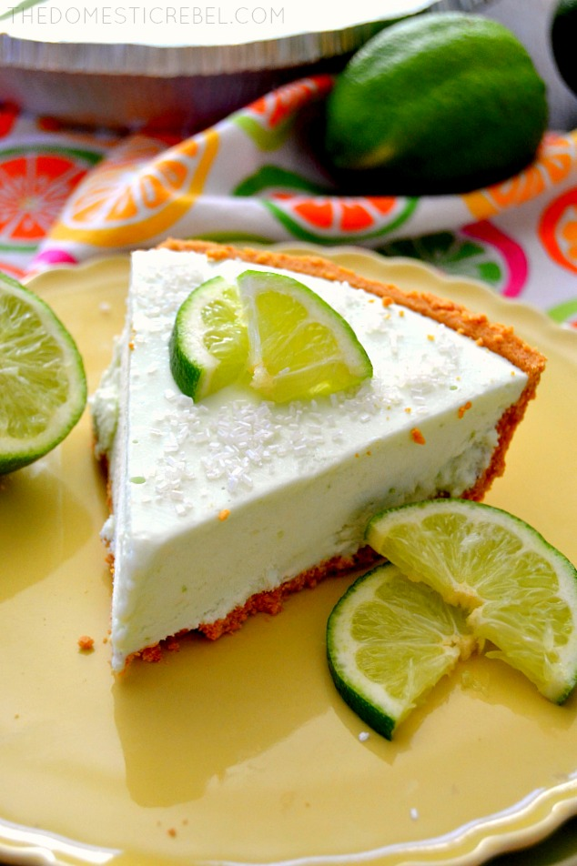 Margarita Cheesecake Pie on green plate with lime wedges and a lime in background