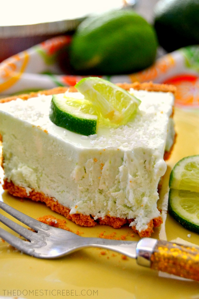 Margarita Cheesecake Pie on green plate with fork, lime wedges and a bite missing