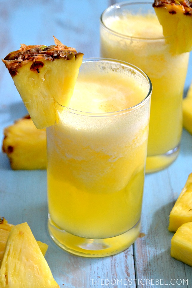 Pina Colada Bellinis in glasses with pineapple wedges on blue background