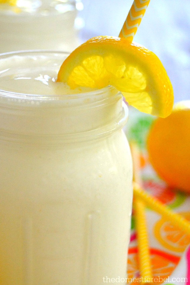 Closeup of Frozen Lemonade in a mason jar with lemon wedge and yellow straw