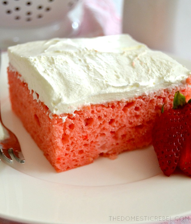 Strawberry Cream Sheet Cake on white plate with fork and sliced strawberry
