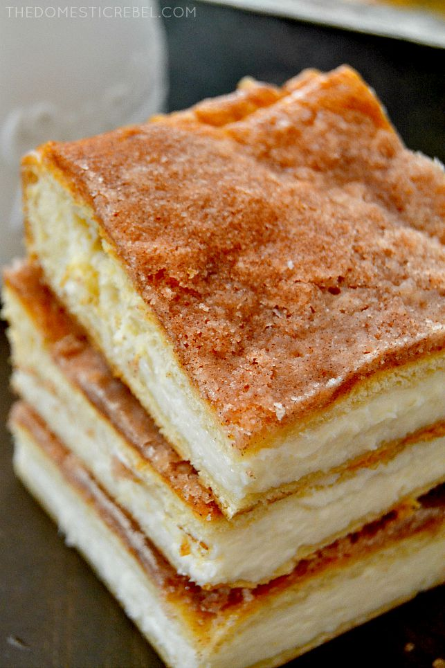 Sopapilla Cheesecake Bars stacked on dark background
