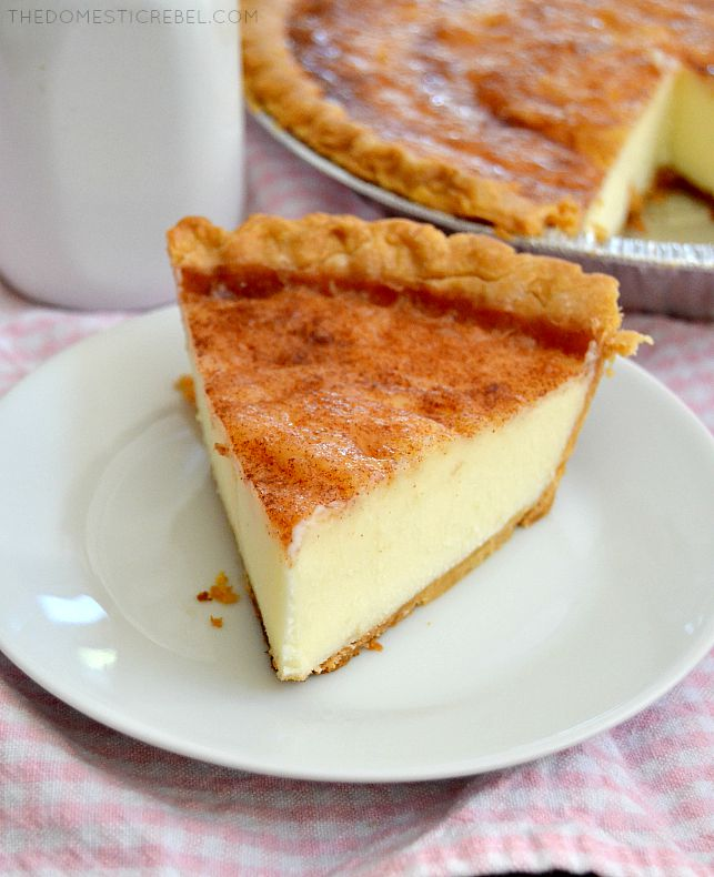 Sugar Cream Pie slice on white plate with pink gingham fabric and pie in the back