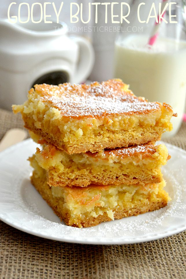 Gooey Butter Cake Bars stacked on white plate with milk glass in background