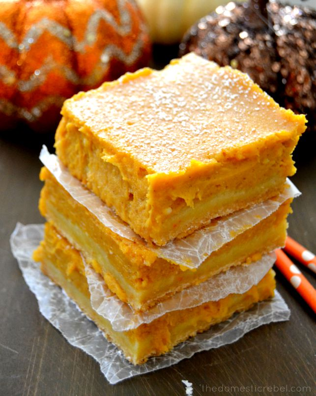 pumpkin gooey bars stacked between parchment layers with pumpkins in back