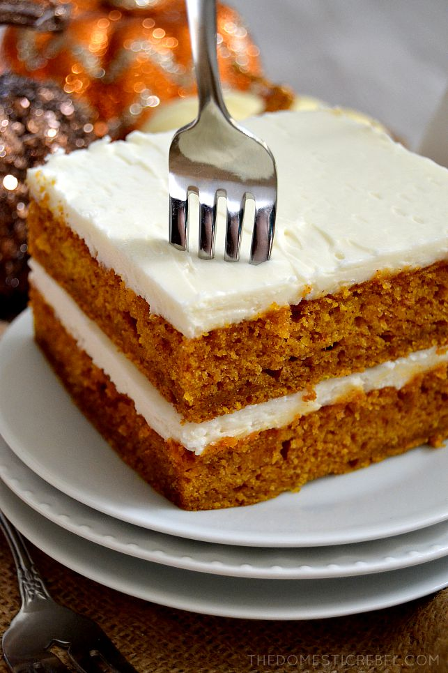 Pumpkin Spice Sheet Cake stacked on a stack of white plates with fork in it