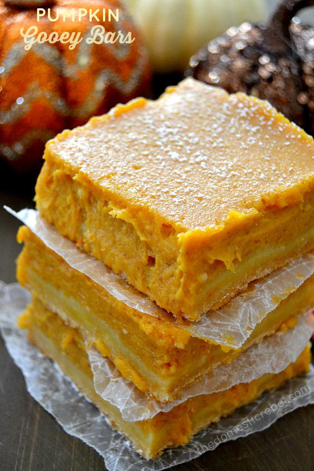 pumpkin gooey bars stacked between parchment with pumpkins in background