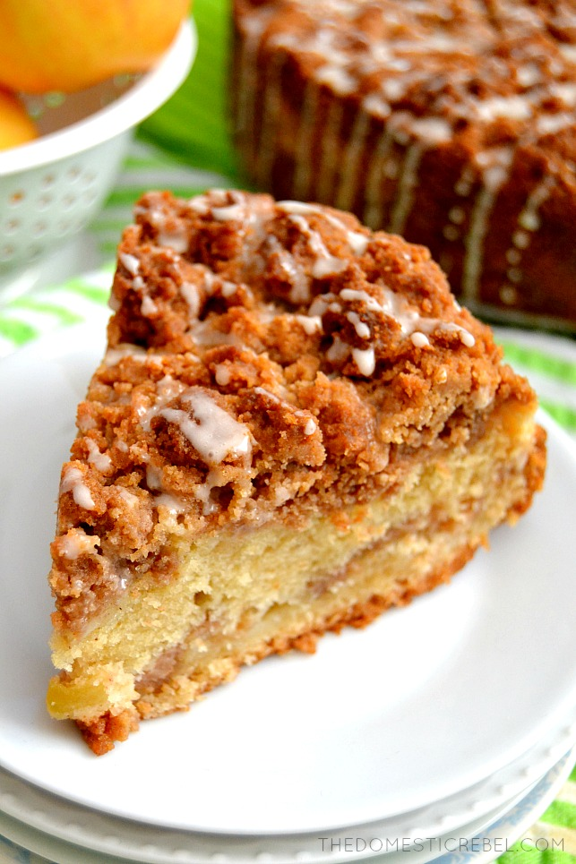 apple cinnamon crumb cake on stack of white plates with cake and apples in background