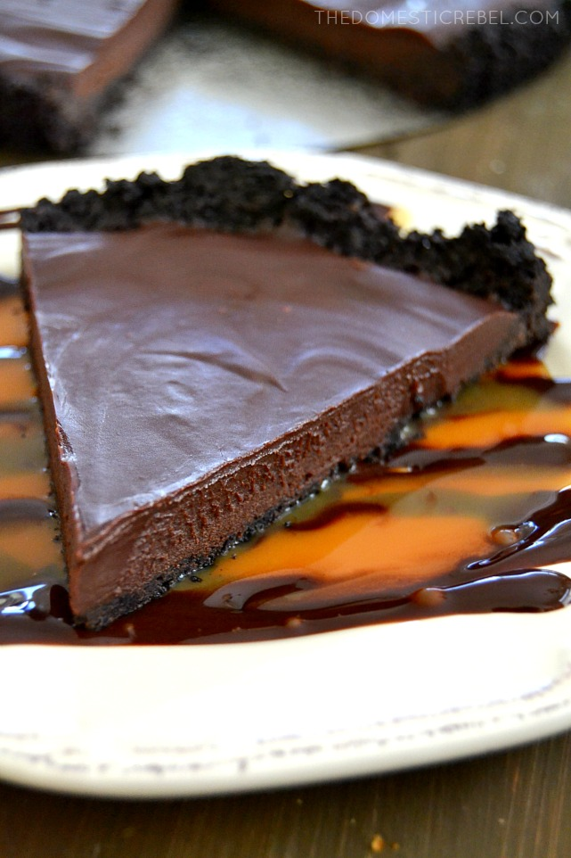 double chocolate ganache pie on white plate with caramel and chocolate drizzle