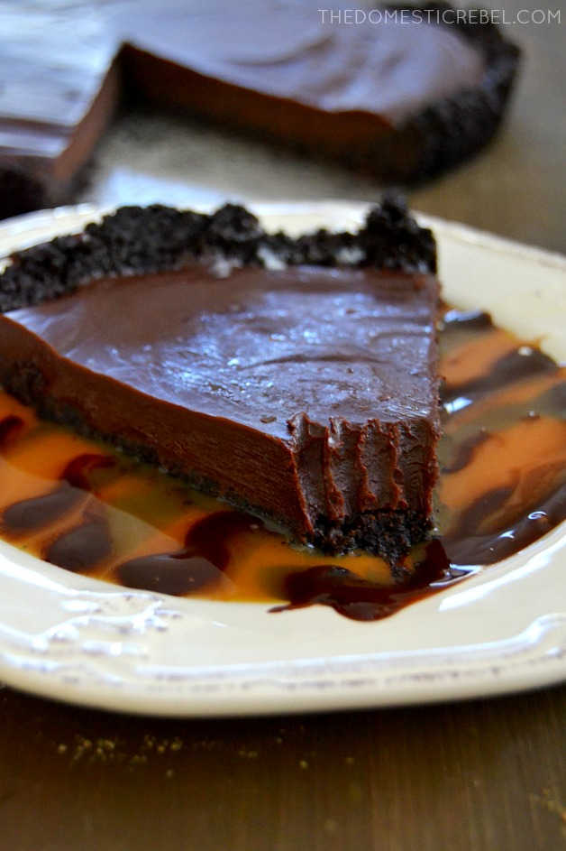 double chocolate ganache pie with bite missing on white plate with caramel and chocolate drizzle