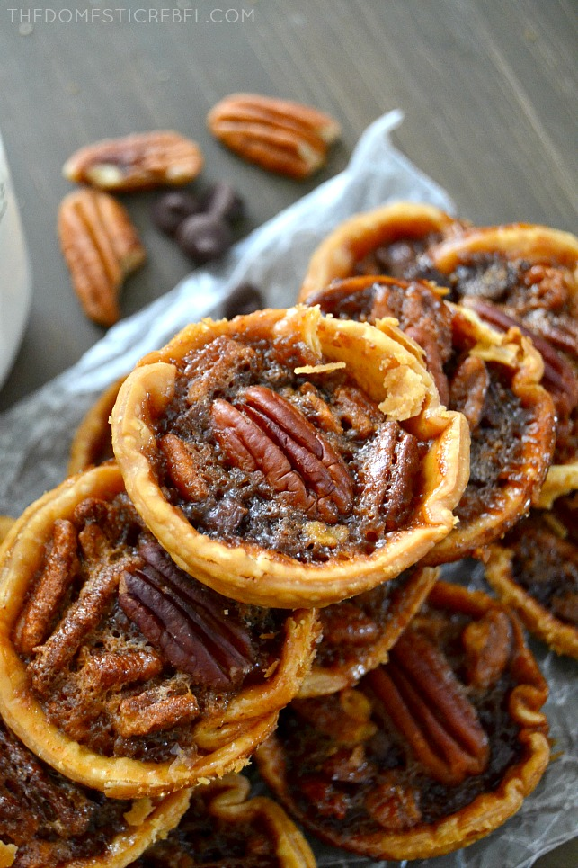 chocolate chip pecan pies stacked on parchment and wood with pecans in background