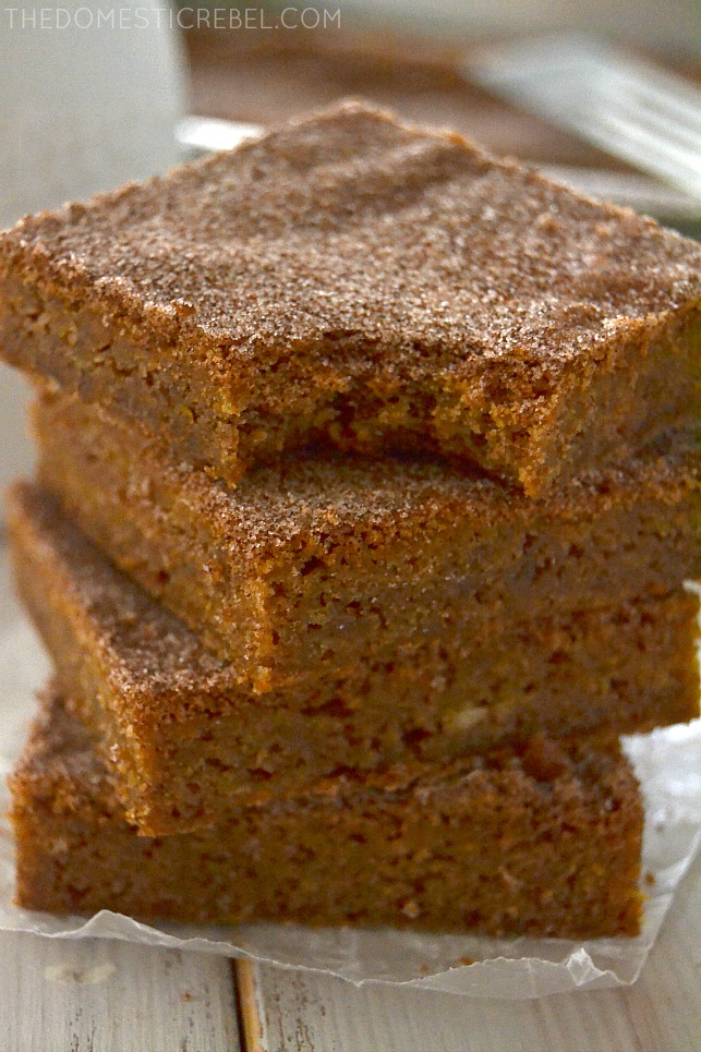 Snickerdoodle Blondies stacked with bite missing on parchment