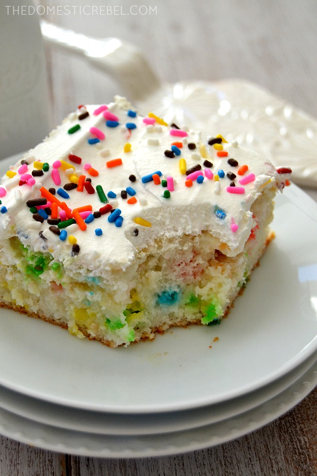 Skinny Funfetti Cake on white plates with bite missing and cake server behind it