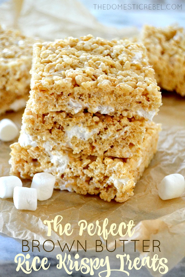 Brown Butter Rice Krispy Treats stacked on parchment with marshmallows