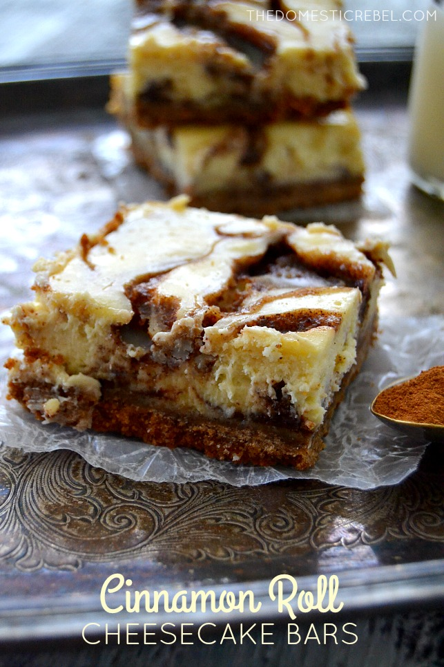 Cinnamon Roll Cheesecake Bars arranged on metal tray with spoonful of cinnamon