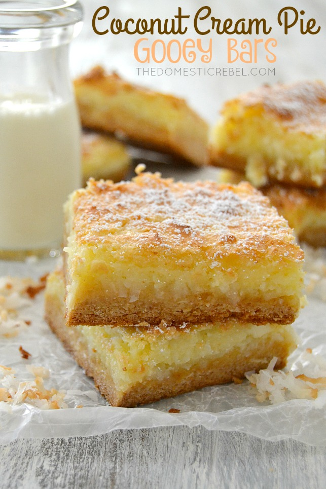 Coconut Cream Pie Gooey Bars stacked on parchment with toasted coconut and milk in background