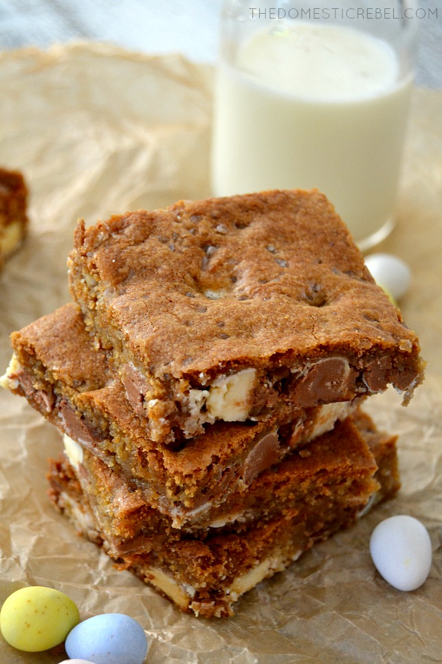 Salted Cadbury Egg Blondies stacked on parchment with glass of milk and candy eggs