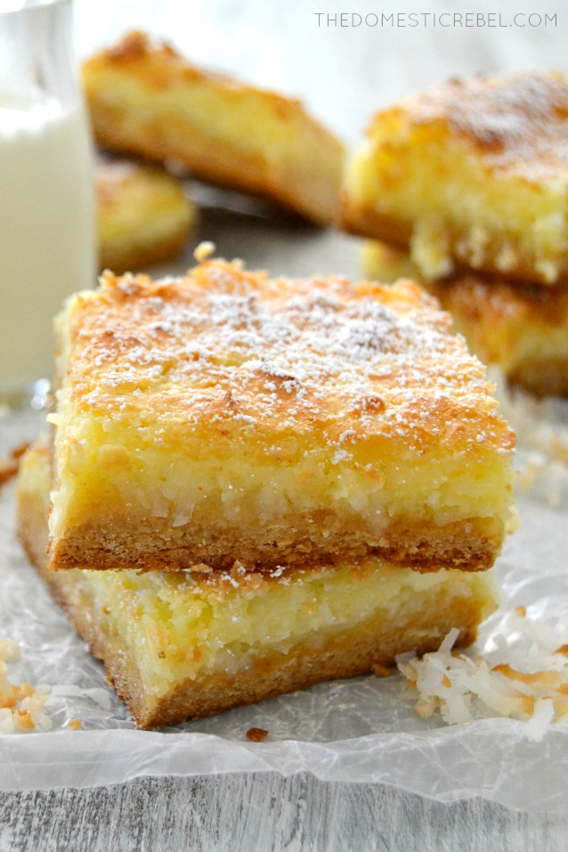 Coconut Cream Pie Gooey Bars stacked on parchment with toasted coconut