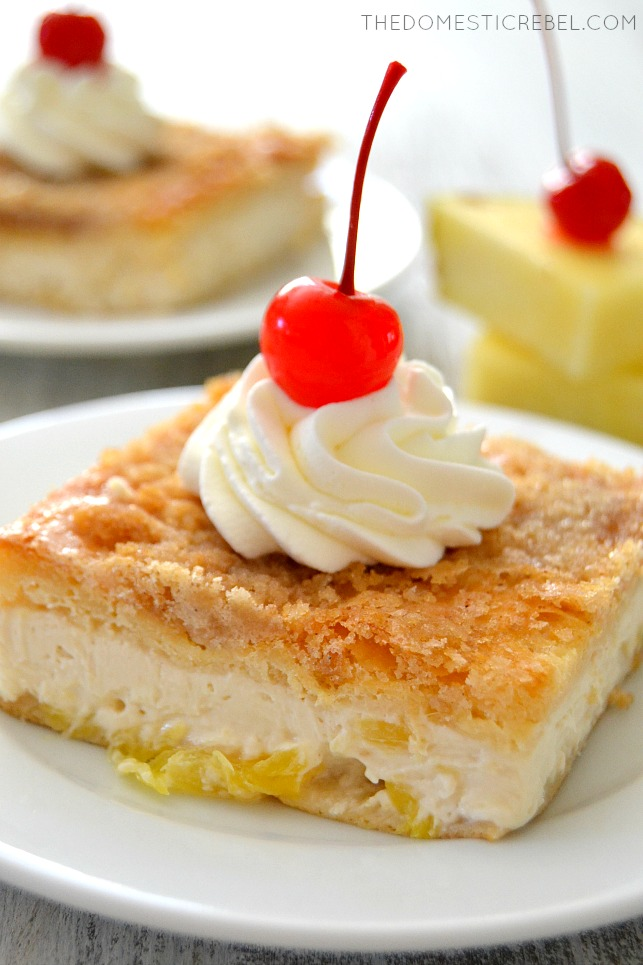 Closeup of Pineapple Upside Down Cheesecake Bars on white plate with pineapple wedges