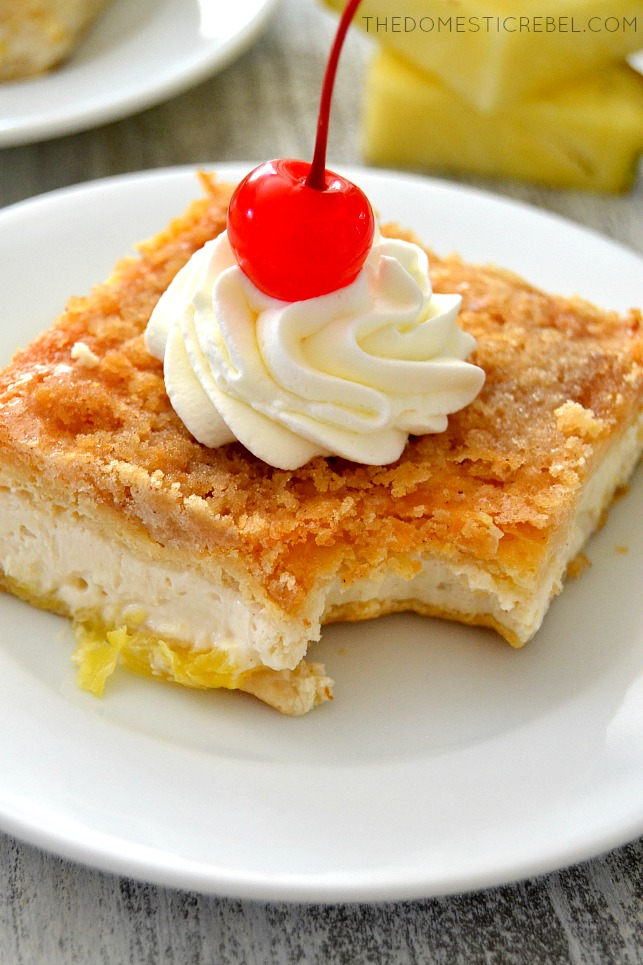 Closeup of Pineapple Upside Down Cheesecake Bars with bite missing on white plate