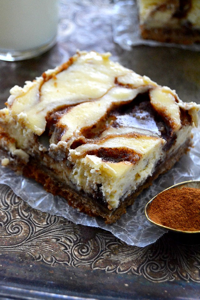 Cinnamon Roll Cheesecake Bars arranged on parchment-lined metal tray with spoonful of cinnamon