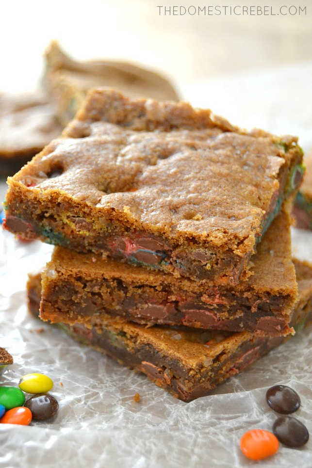 Brown Butter Espresso M&M Blondies stacked on parchment with M&Ms scattered