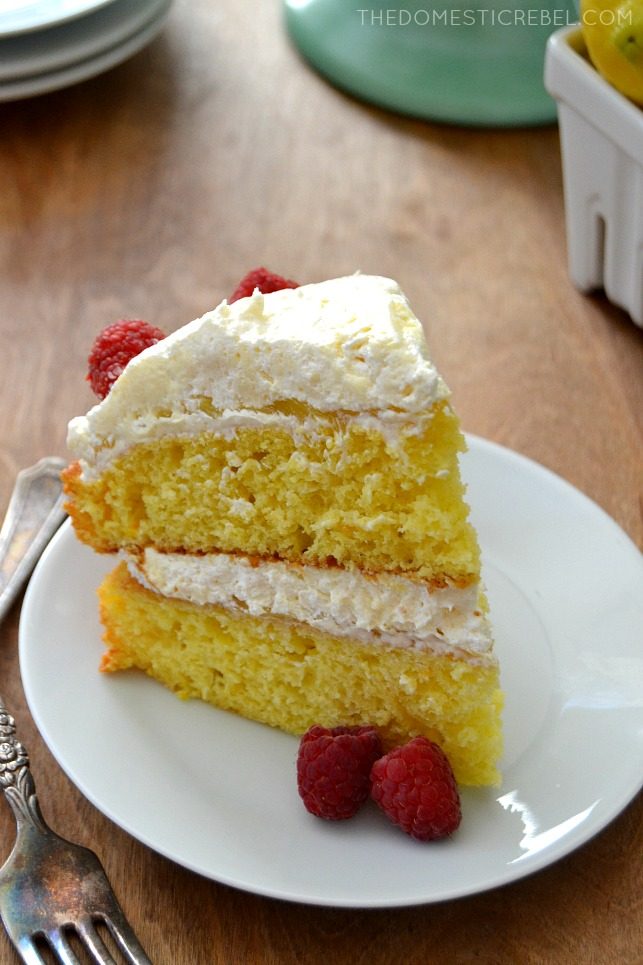 Lemon Layer Cake slice on white plate with forks and fresh raspberries