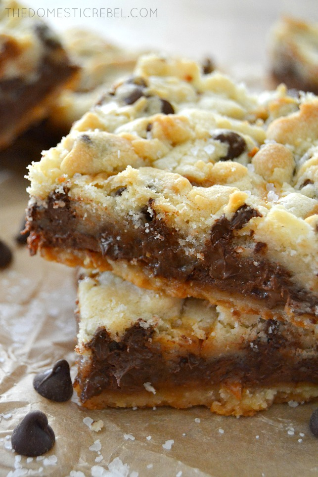 Salted Nutella Caramel Butter Bars stacked on parchment with chocolate chips scattered