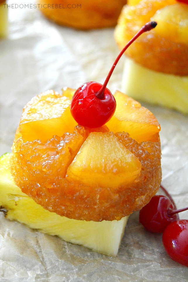 Pineapple Upside Down Cupcakes on a pineapple wedge with cherries