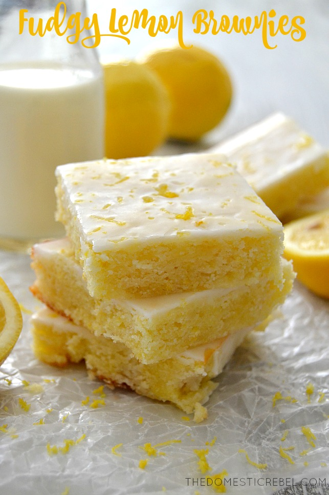 Lemon Brownies stacked on parchment with lemon slices and a glaass of milk
