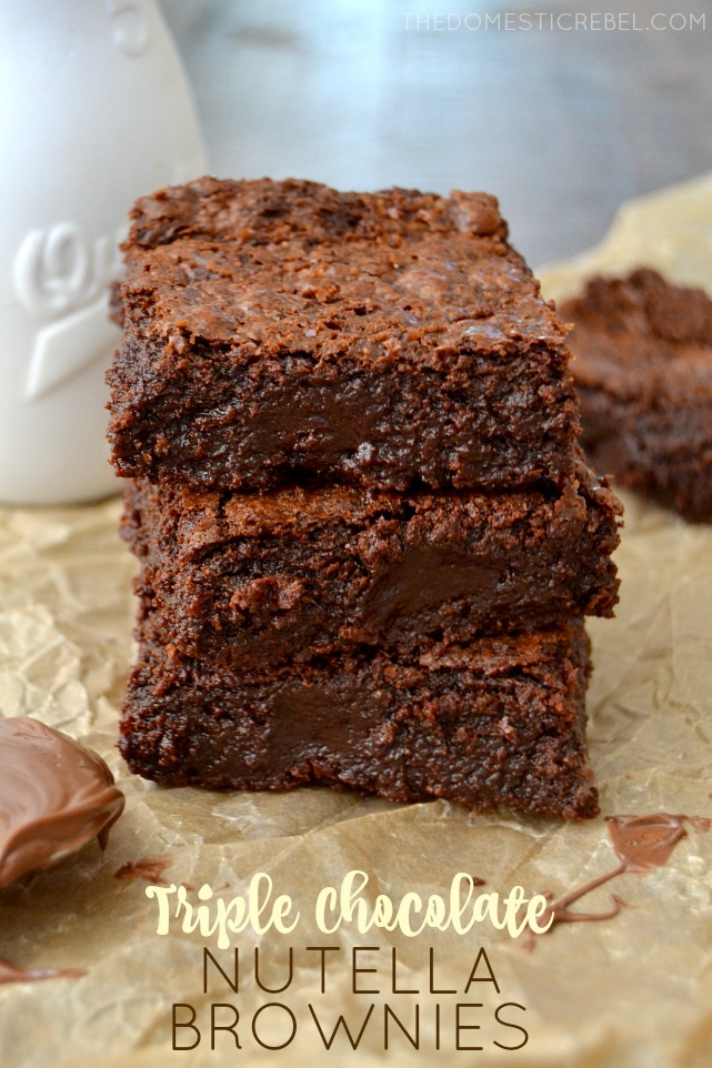 Triple Chocolate Nutella Brownies stacked on parchment paper with milk in background