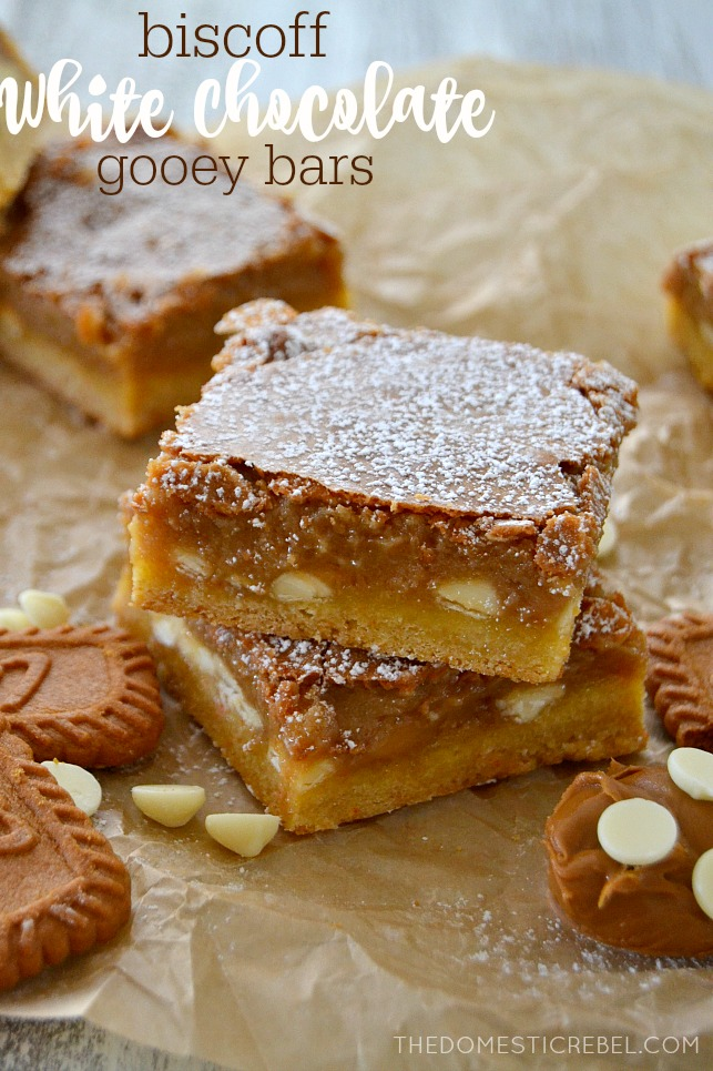 Biscoff White Chocolate Gooey Bars stacked on parchment with white chips and cookies