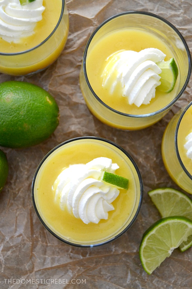 Key Lime Pie Parfaits arranged in glasses on parchment with limes and lime wedges