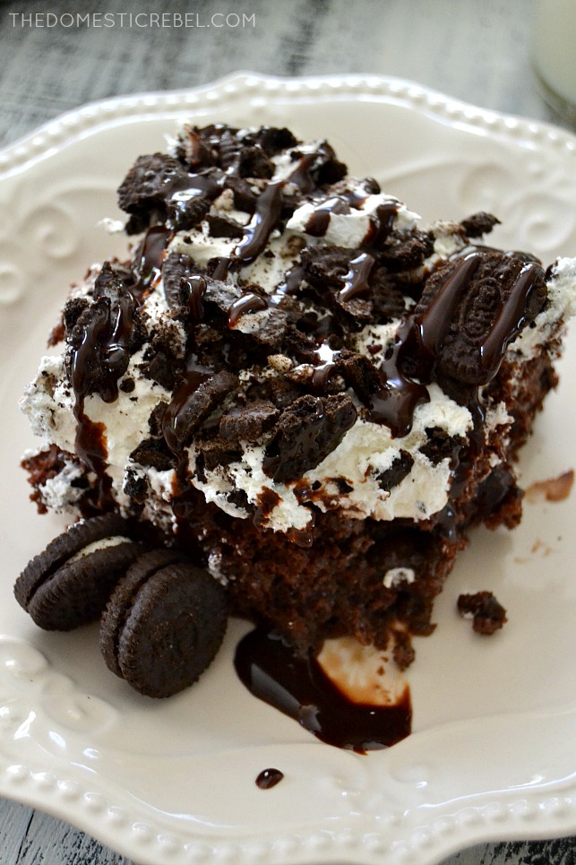Oreo Poke Cake on white plate with Oreo cookies
