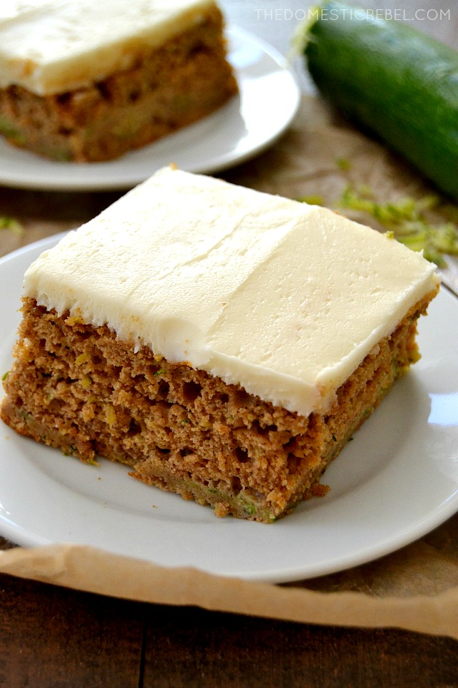 Closeup of Zucchini Cake slice on white plates with zucchini in background
