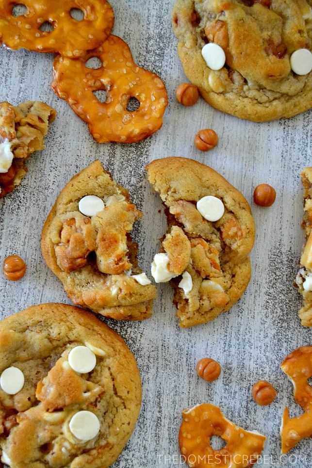 White Chocolate Pretzel Cookies scattered on white wood with pretzels and caramel bits
