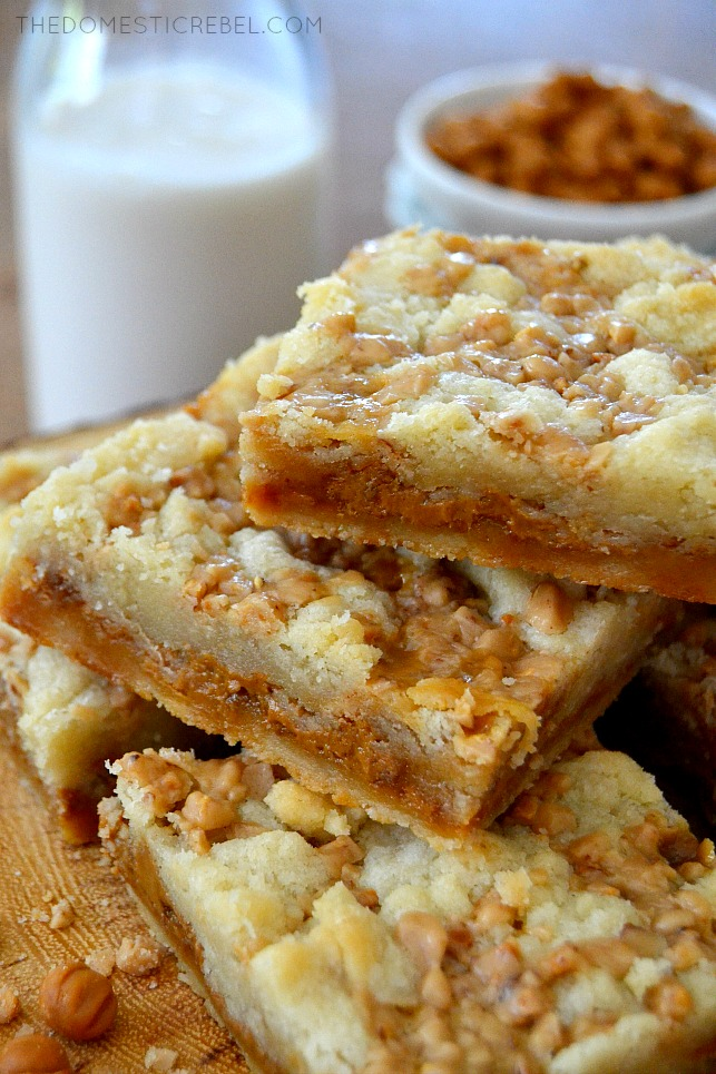 Biscoff Caramel Butter Bars arranged on wood with milk in background