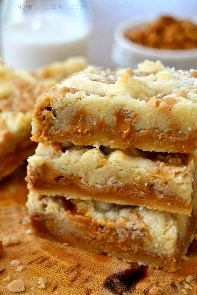 Biscoff Caramel Butter Bars stacked on wood with milk in background