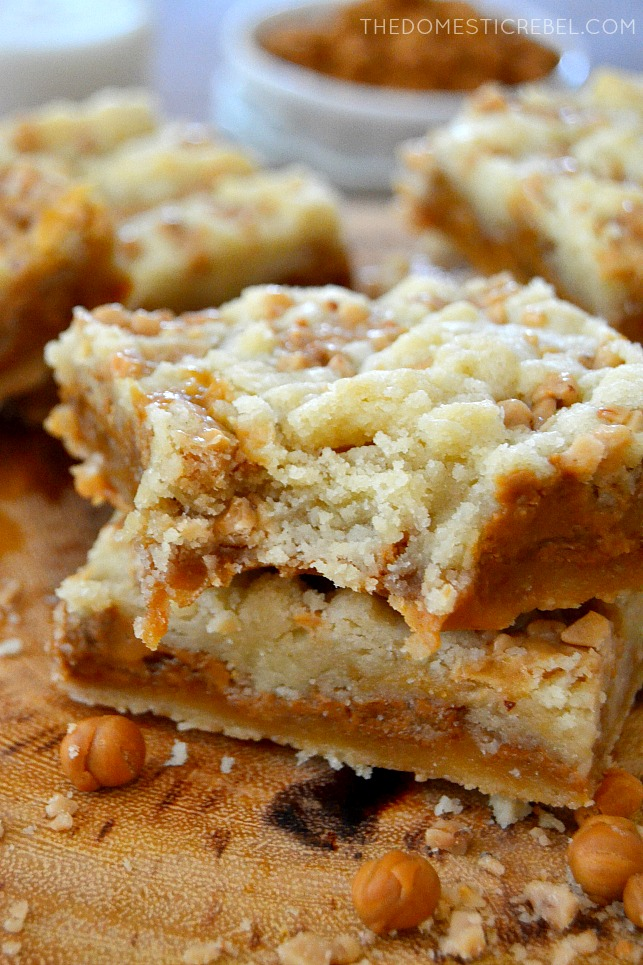 Biscoff Caramel Butter Bars stacked with bite missing on wood