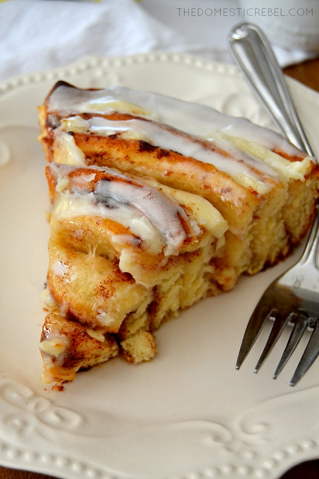Closeup slice of Cinnamon Roll Cheesecake Cake on white plate with forks