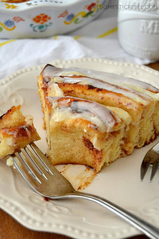 Cinnamon Roll Cheesecake Cake slice on white plate with fork and bite missing