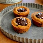 These Salted Ganache Cookie Cups are a 3-ingredient wonder! Chewy chocolate chip cookie cups are filled with a rich and gooey ganache and topped with sea salt. So easy, so impressive!