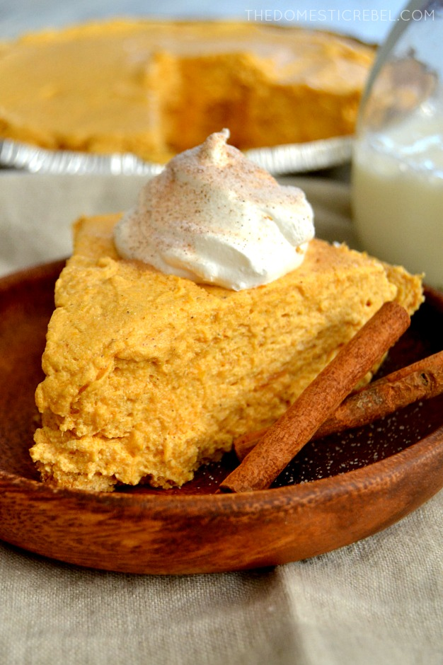 Pumpkin Marshmallow Pie on wood plate with cinnamon sticks and pie in background