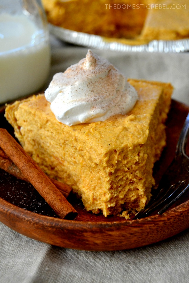 Pumpkin Marshmallow Pie slice with bite removed on wood plate with cinnamon sticks